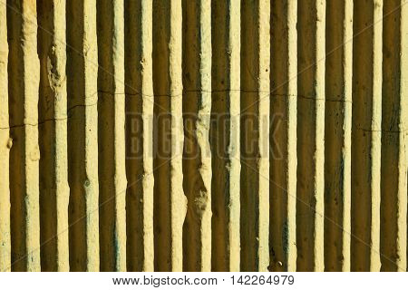 The ribbed surface yellow wall, with vertical edges, under sunlight.