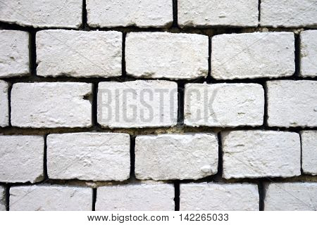 Old wall of bricks painted with white paint, close-up.