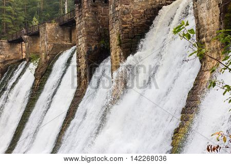Water flowing down the walls of the old small hydropower plants