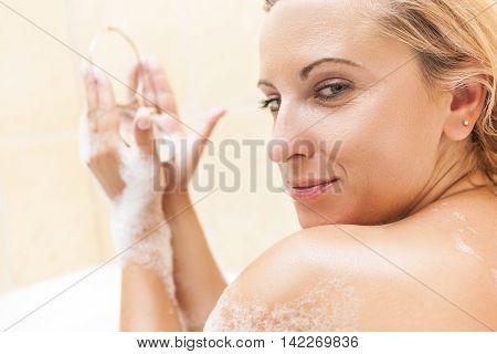 Young Caucasian Blond Female Doing Makeup During Bathing Process.Positive Facial Expression. Skin Treatment Procedure. Horizontal Shot