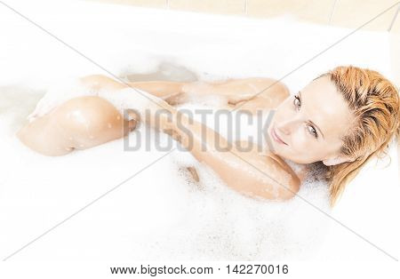 Alluring Sexy Caucasian Blond Female in Foamy Bathtub During Skin and Body Treatment Process.Passionate Look. Horizontal Image Composition