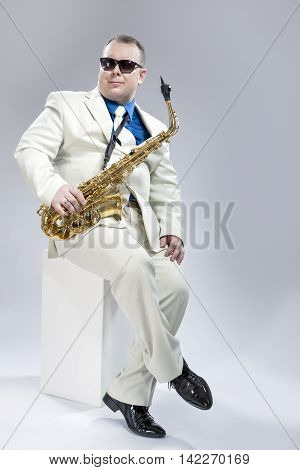Full Length Portrait of Handsome Caucasian Musician With Alto Saxophone Posing In White Suit Against White Background. Wearing Black Sunglasses.Vertical Image Composition
