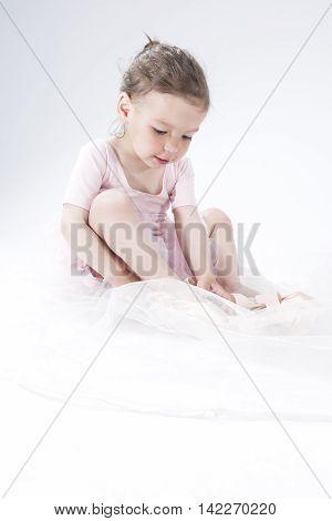 Natural Portrait of Cute Little Ballerina Against White. Vertical Shot