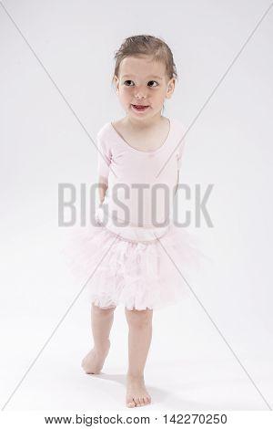 Full Length Portrait of Little Female Caucasian Child. Posing Against White Background. Vertical Image