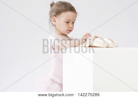 Children Concepts and Ideas. Little Cute Caucasian Girl Poses With Miniature Pointes. Against White. Horizontal Image Orientation
