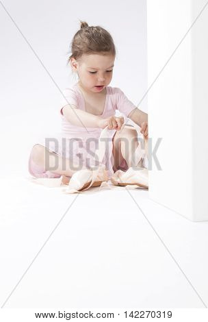 Portrait of Cute Concentrated Caucasian Girl Trying On Miniature Pointes. Sitting on Floor. Against White. Vertical Image Composition