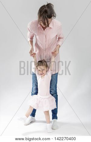 Family Concepts and Ideas. Young Mother and Her Little Cute Daughter Playing Together. Posing Against White. Vertical Image Composition