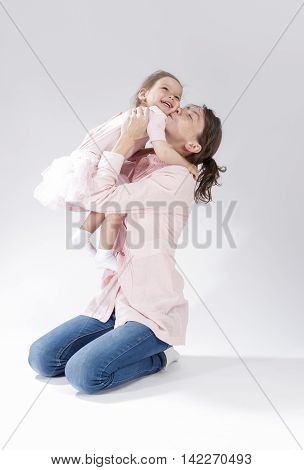 Love and Relationships Concepts. Portrait of Young Mother Kissing Her Child with Positive Expression. Against White. Vertical Image