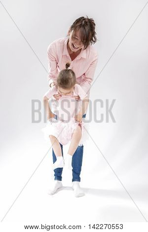 Mother and Little Daughter Together Having Fun and Hugging. Posing Against White. Vertical Image