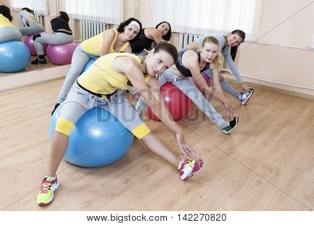 Sport Concepts. Group of Five Female Sportswomen Having Legs Muscles Stretching Exercises With Fitballs. Horizontal Image
