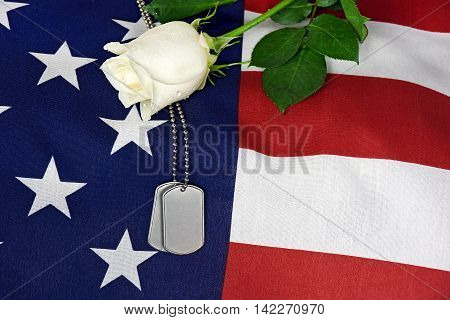 military dog tags and white rose on American flag