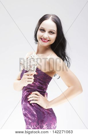 Smiling Sensual Brunette Woman Holding Symbolic Weaved Heart. Posing Over White. Vertical Image Composition