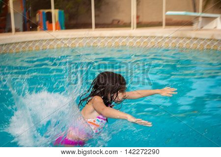 A young girl flying into the water backwards from a pool slide. Her arms are spread out in front of her and her cheeks are puffed out to hold her breath. The water is splashing all around her and there is copy space.