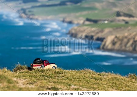 Pickup truck carrying a camera lens with a New Zealand coastline in the background.