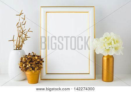 Frame mockup with ivory hydrangea in the golden vase white vase and golden flower pot. Poster white frame mockup. Empty white frame mockup for presentation artwork.