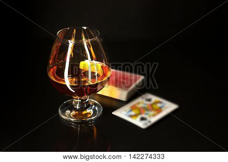 Whiskey glass and playing cards. Cognac glass. Brandy glassful. Cognac france. Playing cards and scotch drink.