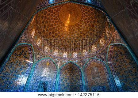 ISFAHAN IRAN - MAY 2 2016: interior of the dome and central hall of the Sheikh Lotfollah Mosque in persian style. The Mosque built in 1619 and now is a UNESCO World Heritage Site.