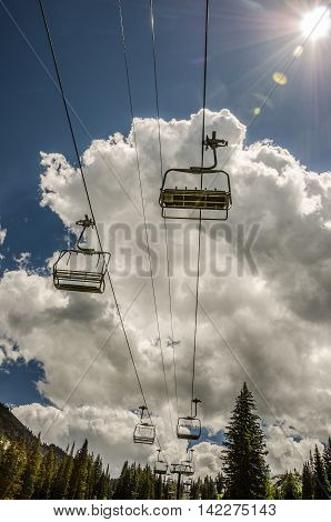 Empty chairs at a ski area in the summer move overhead as if they are in the clouds