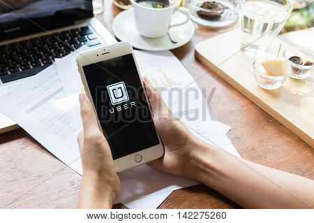 CHIANG MAITHAILAND - MAY 092015 : A woman hand holding Uber app showing on iphone 6 plus in coffee shopUber is smartphone app-based transportation network.