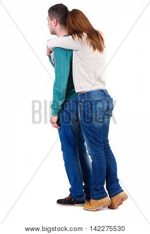 Back view of young embracing couple (man and woman) hug and look into the distance. backside view of person.  Isolated over white background. The girl in warm jacket standing on tiptoes hugging man