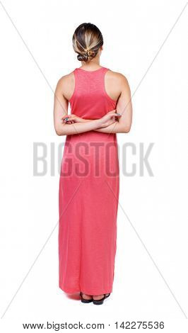 back view of standing young beautiful  woman.  girl  watching. Rear view people collection.  backside view of person. A slender woman in a long red dress is standing with his hands behind his back.