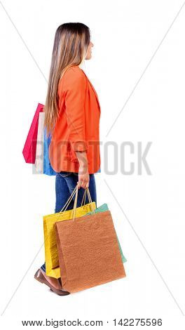 side view of going  woman  with shopping bags . beautiful girl in motion.  backside view of person.  Rear view people collection. Isolated over white background.  girl in a red jacket goes to the side