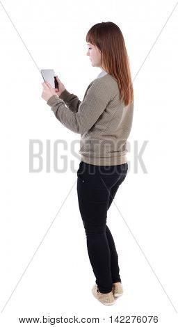 back view of standing young beautiful  woman  using a mobile phone. girl  watching. Rear view people collection.  backside view of person.  Isolated over white background. Sad girl in a gray sweater