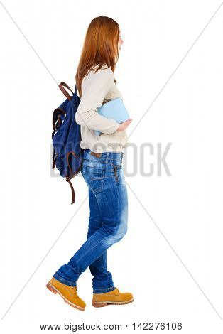 Girl comes with  stack of books. side view. Rear view people collection.  backside view of person.  Isolated over white background. The girl with the blue backpack in a white blouse goes right with a