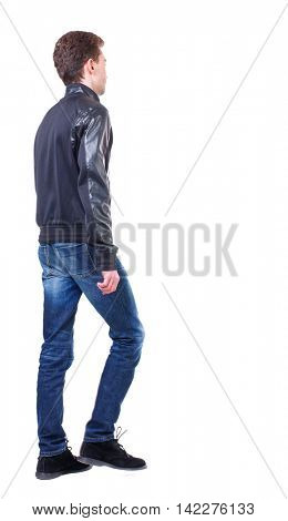 Back view of going  handsome man. walking young guy . Rear view people collection.  backside view of person.  Isolated over white background. Curly guy in a black leather jacket goes sideways.