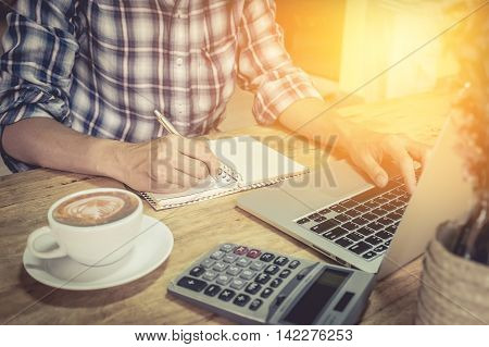 close up hand of business man using laptop computer and write on notebook with cup of coffee and calculator on wooden desk outdoor office with morning light. vintage filter effect.