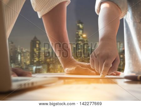 Close up Businessman and woman hand discussing on stockmarket charts in office with hong kong night cityscape background