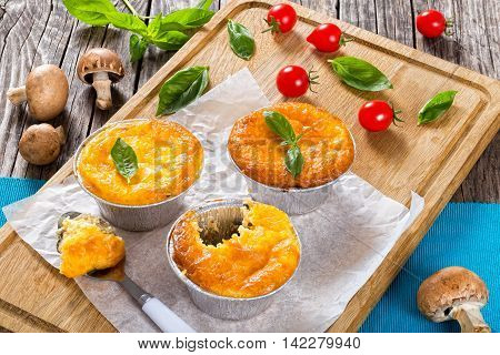 French cuisine- julienne. Mushroom chicken and cheese gratin in Mini Baking cups decorated with basil leaves on wooden cutting board with spoon authentic recipe close-up