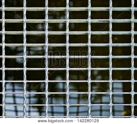 metal mesh of a manhole of the water network or the sewer system of the city