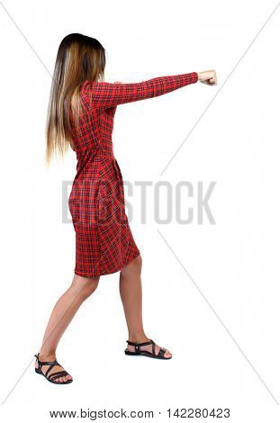 skinny woman funny fights waving his arms and legs. Isolated over white background. The girl in red plaid dress stands sideways and punches.