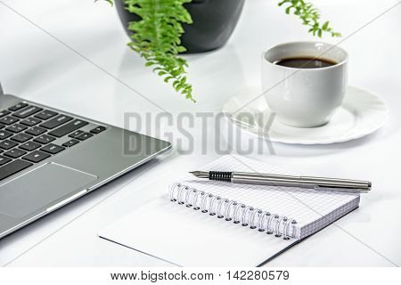 Sleek metal laptop and pen with notepad on a white desk and coffee in the background