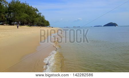 small waves breaking on a long, sandy beach, line of pine trees stretching to the horizon, two islands and several ships on the horizon, several distant people on the beach in street clothes, Songkhla, Thailand