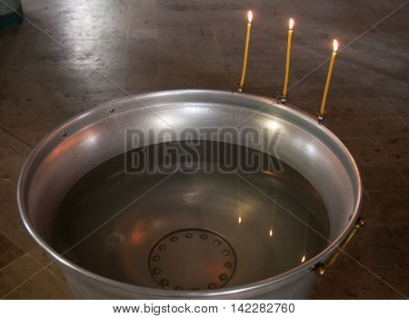 Bowl for the rite of baptism in the Orthodox Church with candles