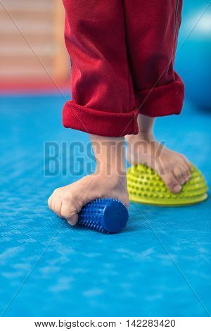 Flat feet physical therapy - Little boy stepping onto spiked rubber roller