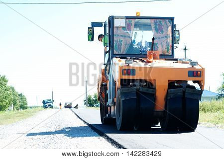 HALBSTADT, RUSSIAN FEDERATION - AUGUST 8, 2016: Roller paving new asphalt in the countryside