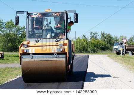 HALBSTADT, RUSSIAN FEDERATION - AUGUST 8, 2016: Making new asphalt with roller the countryside