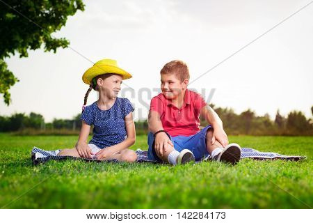 A girl and a boy sitting on grass on a sunny day