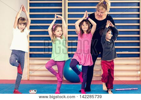Group of little children with teacher on physical education class. Trying to stand on one leg keeping balance