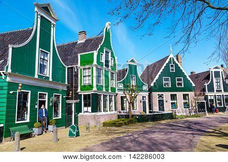 Zaanse schans, Netherlands - April 1, 2016: Zaanse Schans, traditional village, tourists walking, North Holland, green houses against blue cloudy sky