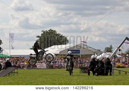 WEEDON, UK - AUGUST 29: Members of the Royal Signals White Helmets display team demonstrate a jump stunt for the public at the Bucks County show on August 29, 2013 in Weedon