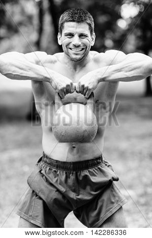 Cross fit athlete exercising with kettle bell. Black and white