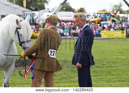 WEEDON, UK - AUGUST 29: Former National Hunt Champion jockey John Francome MBE inspects a young horse while on judging duties at the Bucks County Show on August 29, 2013 in Weedon