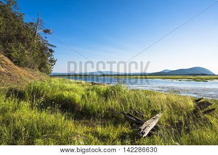 Widely stretched mouth of the river Kika in the place where it flows into lake Baikal. In the distance beyond the river are seen the tops of the low mountains surrounding lake Baikal.