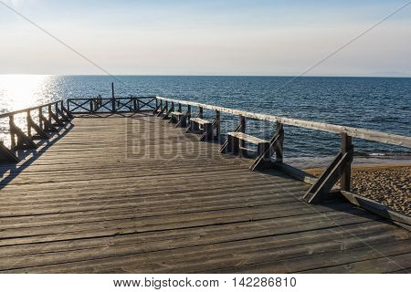 Old wooden pier in the village Gremyachinsk on the shore of lake Baikal has long been not accepting ships, but I love to watch sunsets by the locals.