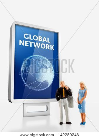 Miniature people- people in front a billboard with Blue globe  about global network