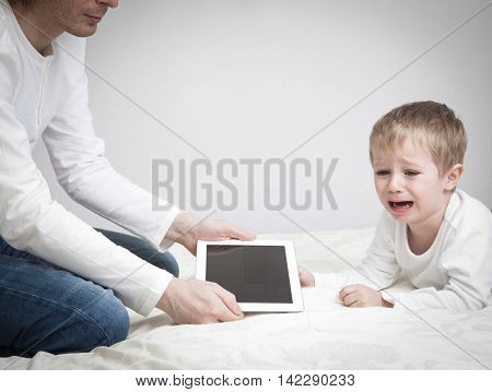 computer addiction, parent taking out touch pad from crying child